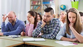 Bored students sitting at lesson. Portrait of bored and tired adult students sitting at lesson in classroom Royalty Free Stock Photos