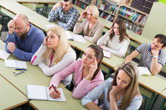 Bored students sitting at lesson. Bored unhappy adult students sitting at lesson in classroom Royalty Free Stock Photos