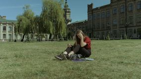 Nervous female student concerned about hard exam. Bored of studying sad beautiful long brown hair female student sitting on campus lawn thinking of exam stock video