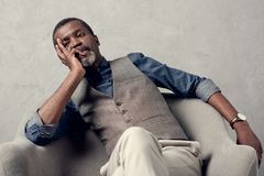 Bored stylish african american man. In waistcoat sitting in armchair royalty free stock photo