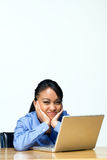 Bored Teen Girl With Laptop Computer - Horizontal. Teen girl looking bored types on a laptop computer as she sits at a desk. Horizontally framed photograph royalty free stock photography