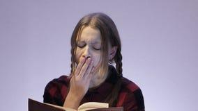 Bored teen girl reading book. 4K UHD stock video footage
