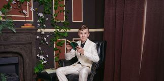 Bored teen student guy in white business suit sitting in a chair with a book by the fireplace stock photo