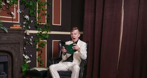 Bored teen student guy in white business suit sitting in a chair with a book by the fireplace royalty free stock images