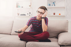 Bored teenage boy watching tv at home. Boring television, disappointed teenager boy holding remote control, watching TV show Royalty Free Stock Image
