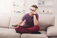 Bored teenage boy watching tv at home Royalty Free Stock Image