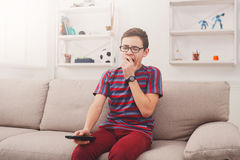 Bored teenage boy watching tv at home. Boring television, sleepy teenager boy holding remote control, watching TV show Royalty Free Stock Photo