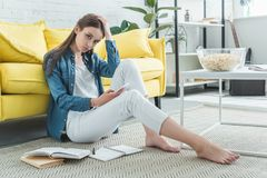 bored teenage girl holding smartphone and looking at camera while sitting on carpet and studying stock photos