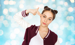 Bored teenage girl making finger gun gesture Royalty Free Stock Photo