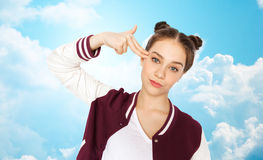 Bored teenage girl making finger gun gesture Royalty Free Stock Images