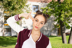 Bored teenage girl making finger gun gesture Stock Images