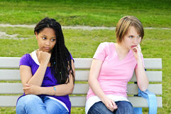 Bored teenage girls. Two bored teenage girls sitting on bench Stock Images