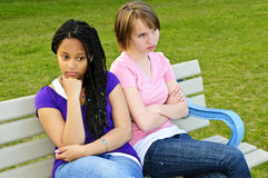 Bored teenage girls. Two bored teenage girls sitting on bench Stock Image