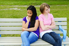Bored teenage girls. Two bored teenage girls sitting on bench Royalty Free Stock Photos