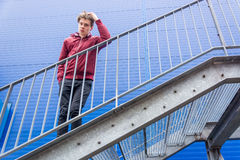 Bored teenager boy standing on stairs over blue building Royalty Free Stock Image