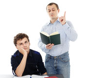 Bored teenager during homework help from father. Teenage student displaying boredom sitting at his deks, while his father is lecturing Stock Photo