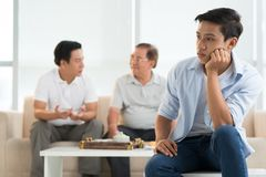 Bored teenager. Portrait of bored teenager and his father and grandfather talking in background Stock Photography
