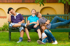 Bored teenagers sitting and lying on the bench royalty free stock photography