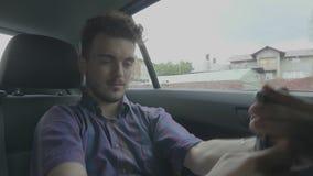Bored tienermens die met smartphone rond het maken van grimassen voor de gek houden neemt selfie pics terwijl hij die op uberauto stock video