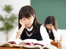 bored tienerstudent die op stapel van B rusten stock afbeeldingen