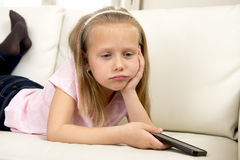 Bored and tired blond little girl on home sofa using internet app on mobile phone stock images