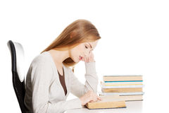 Bored and tired casual student woman sitting by the desk and lea Royalty Free Stock Photo