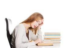 Bored and tired casual student woman sitting by the desk and lea Royalty Free Stock Image