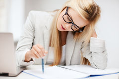Bored and tired woman. Business and education concept - indoor picture of bored and tired woman taking notes Stock Photo