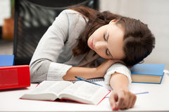 Bored and tired woman sleeping on the table Royalty Free Stock Photography