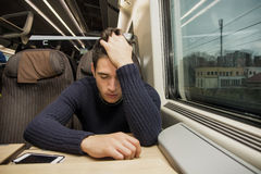 Bored tired young man traveling on a train. Sitting in a passenger coach with his head resting on his hand and eyes closed Stock Images