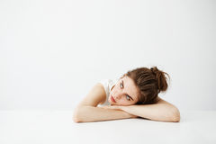 Bored tired young pretty girl with bun thinking dreaming lying on table over white background. Copy space stock photo