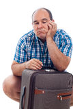 Bored traveller man with luggage. Bored traveller tourist man waiting with luggage, isolated on white background Stock Photo