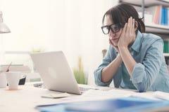 Bored vrouw die met haar laptop werken Stock Foto's