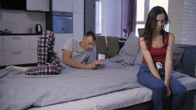 Bored vrouw door echtgenoot wordt genegeerd die smartphone gebruiken die stock footage