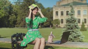 Bored vrouwelijke student aarzelend om openlucht te bestuderen stock video