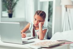 Bored weary small dissatisfied Afro-American child doing lessons. Doing lessons. Bored weary small dissatisfied Afro-American child with brown long braids stock photography