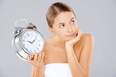 Bored woman with an alarm clock in her hand Royalty Free Stock Photos