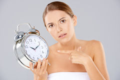 Bored woman with an alarm clock in her hand Royalty Free Stock Images