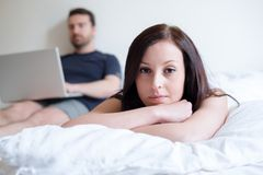 Bored woman and couple lying in the bed Royalty Free Stock Image
