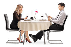 Bored woman on a date with a man. Bored women sitting on a date with a men playing on a tablet isolated on white background stock images