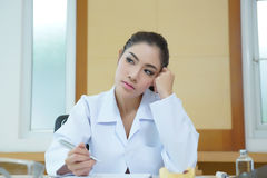 Bored woman dentist looking very boring at her desk Royalty Free Stock Photography