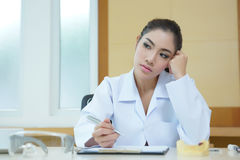 Bored woman dentist looking very boring at her desk.  Royalty Free Stock Images