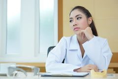 Bored woman dentist looking very boring at her desk Stock Photos