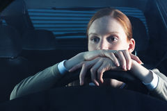 Bored Woman Driver. A young female driver being bored behind the steering wheel in her car. This is a nighttime scene Royalty Free Stock Photography