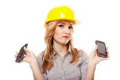 Bored woman engineer holding two cell phones Stock Image