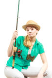 Bored woman with fishing rod, spinning equipment Royalty Free Stock Photo