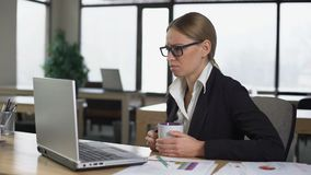Bored woman having coffee break in office, dissatisfied with work, lack of ideas. Stock footage stock video footage