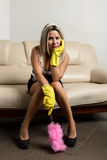Bored woman or housewife sitting on a master couch with rubber gloves Stock Photography