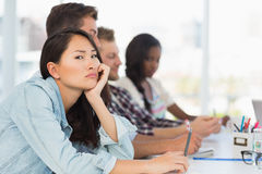 Bored woman looking at camera during a meeting. Bored women looking at camera during a meeting in creative office Stock Image