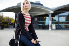 Bored Woman With Mobile Phone Sitting On Luggage Outside Station Stock Image